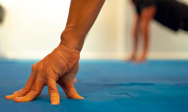 Mão apoiada no chão sobre as pontas dos dedos