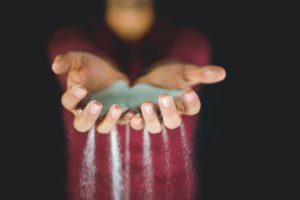homem com as mãos unidas e areia escorrendo entre os dedos