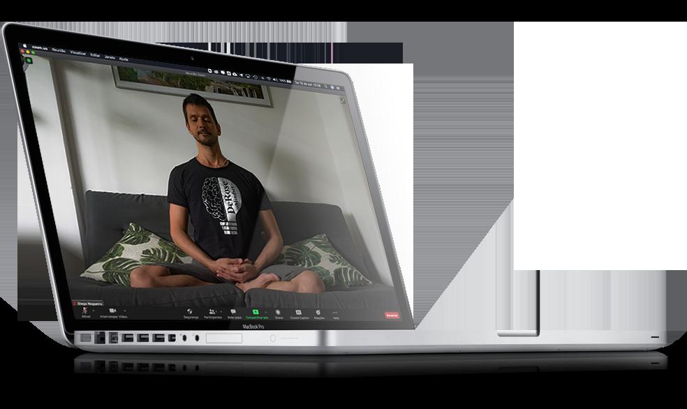 Macbook aberto com imagem na tela de um homem praticando meditação