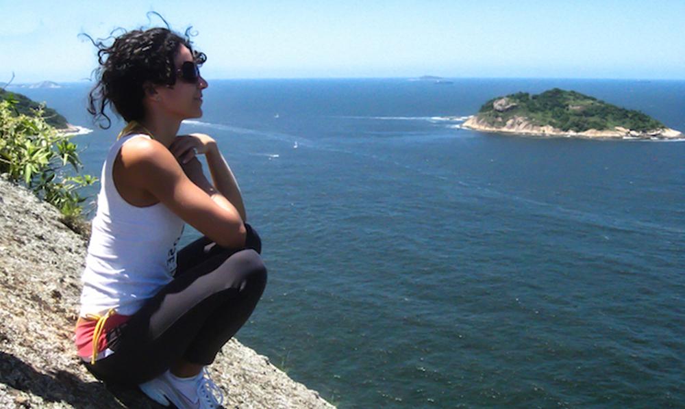 Mulher sentada no alto de uma montanha contemplando o mar