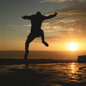 Homem saltando perto da água com o pôr do sol ao fundo.