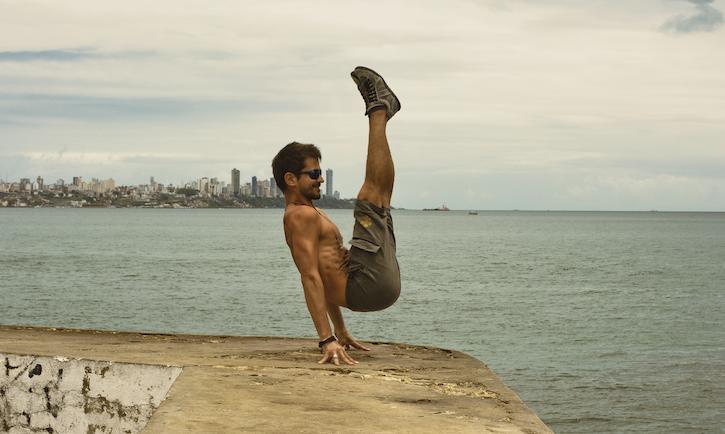 Homem sobre uma mureta com mar de fundo, executando uma técnica de elevação do corpo sobre a ponta dos dedos.