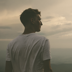 Homem de perfil, vestindo camiseta branca olhando a paisagem